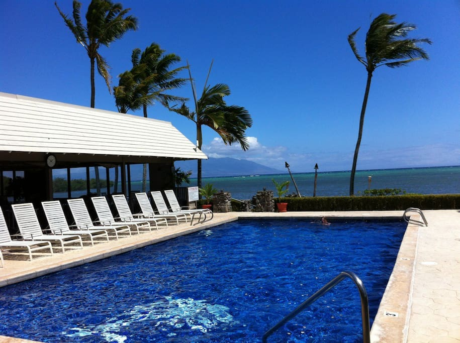Wavecrest pool with Maui in background and large covered clubhouse on left with large glass picture windows at waters edge