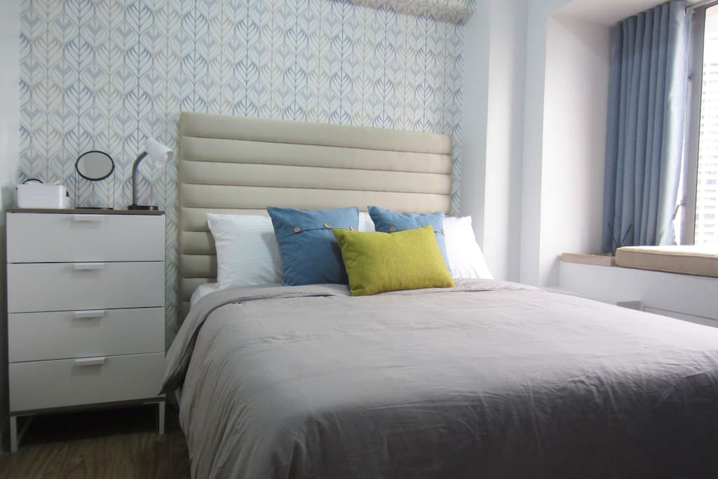 Private bedroom with bedside dresser and reading lamp