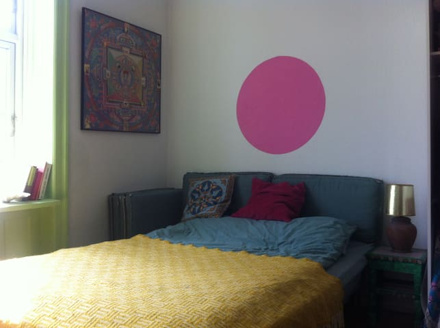Queen-size bed with a peaceful pink circle above the bed.