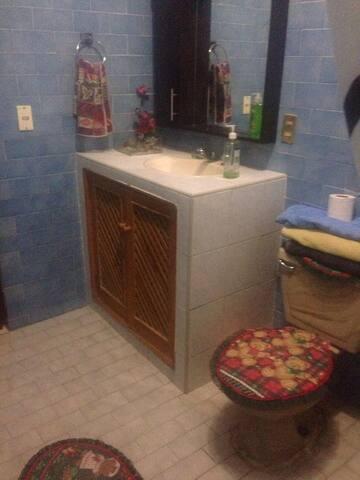 El baño se encuentra a un lado del cuarto, en el pasillo.