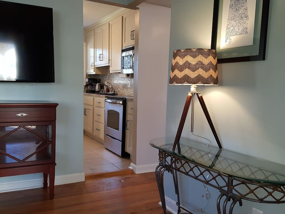 The living room has a large Smart TV and is open to the dining room and kitchen.