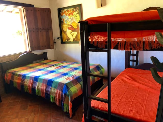 Bedroom with a double bed and bunk bed with a shared bath