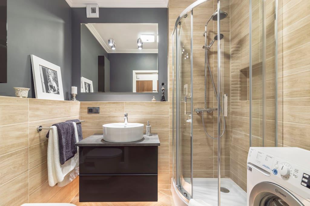Nowoczesna, dobrze oświetlona  łazienka z wygodnym prysznicem i pralką. Na Gości czeka suszarka do włosów, mydło, żel pod prysznic, szampon, waciki, środki czystości, kapsułki do prania i płyn zmiękczający, ręczniki, papier toaletowy i apteczka 1-ej pomocy
