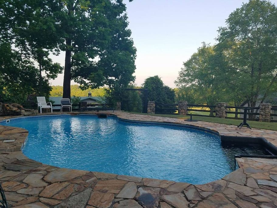 In a picturesque remote setting (beside the cottage) overlooking the lower barn, pastures and woodlands... This stone decked in-ground pool boasts a waterfall, spacious outdoor seating and peaceful serenity.
