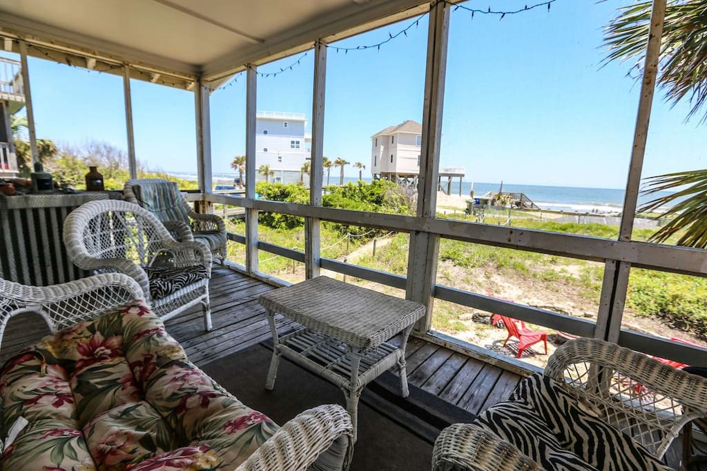 The screened porch is a little slice of heaven with its rustic furniture and unobstructed beach views.