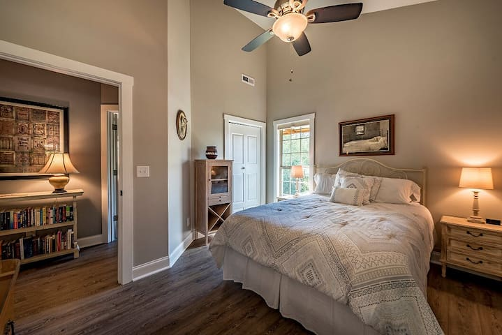 """Bedroom 2, queen-size bed, cordless cellular shades.  Note the """"take one, leave one"""" book collection in the hallway."""