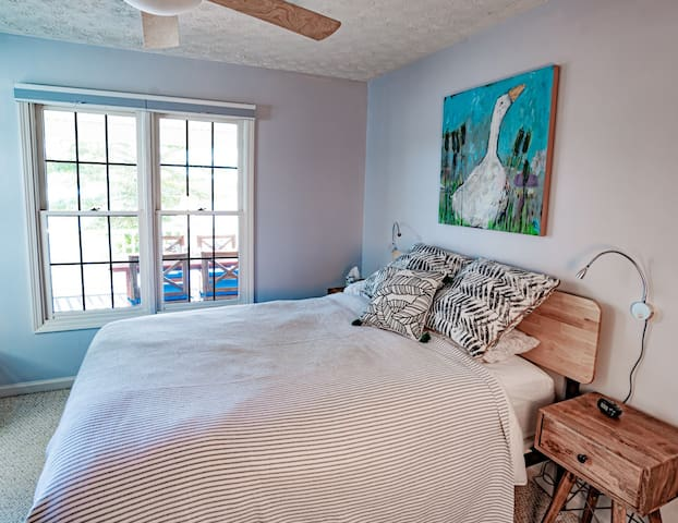 Guest room with queen bed and view of lake