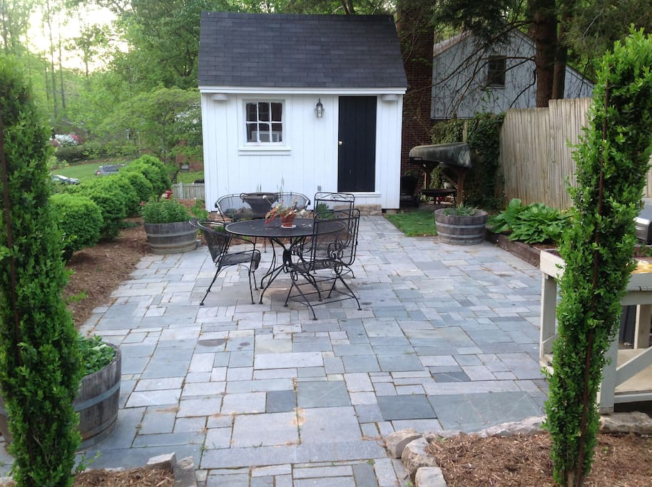 Soapstone Patio with mature boxwoods, fountain and grill.