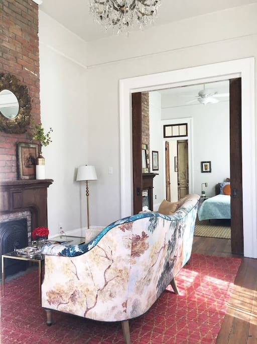 Classy and lovely living room that has 14 foot ceilings and pocket doors to the first bedroom