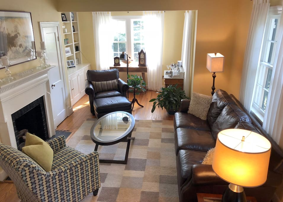 Comfortable living room with leather couch and chair/ottoman.