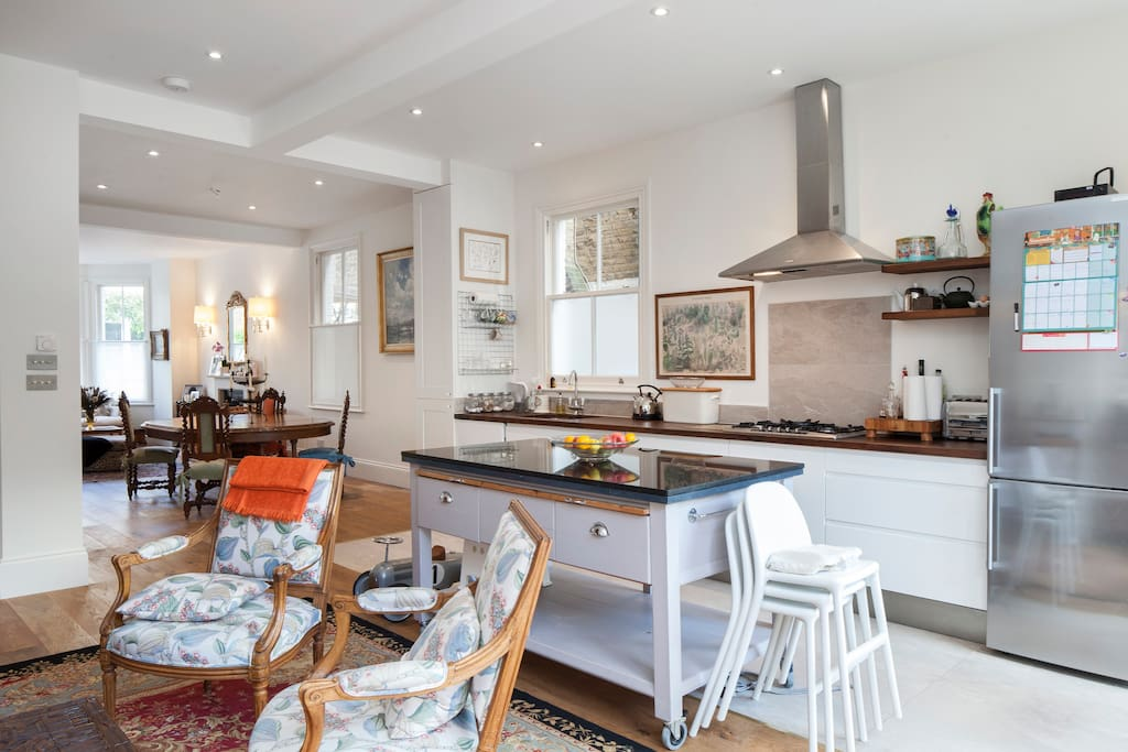 The gorgeous high ceilings, neutral palette, and tall windows throughout give this open space a really airy feeling and also allows guests to spread out onto the garden for al fresco dining under the canopy for extra privacy or a bbq on the patio