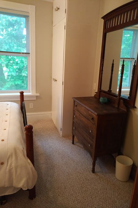Queen bedroom with window and antique dresser