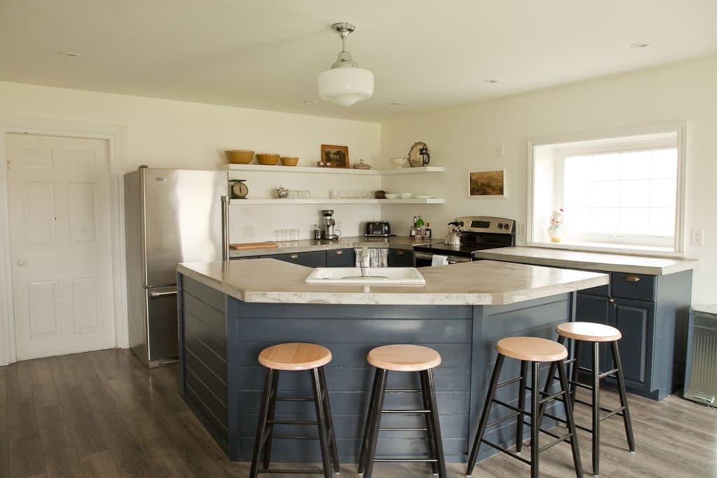 Spacious kitchen with breakfast bar, large farm sink, and dishwasher