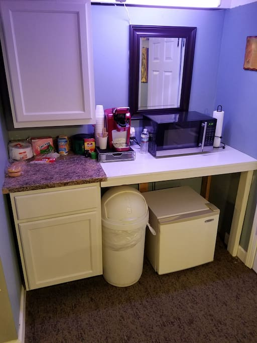 Breakfast area with fridge, microwave, Keurig and various other breakfast items.