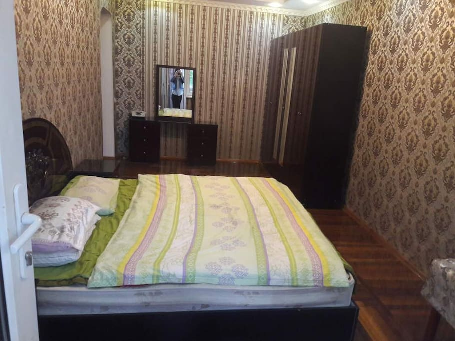 Bedroom with king size bed, wardrobe, mirror table, two (bed) side drawers and small table in the corner