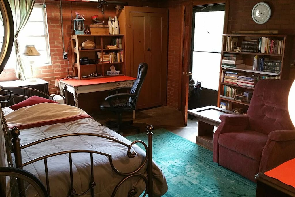 day bed, recliner, coffee table, writing table, shelves, basement door