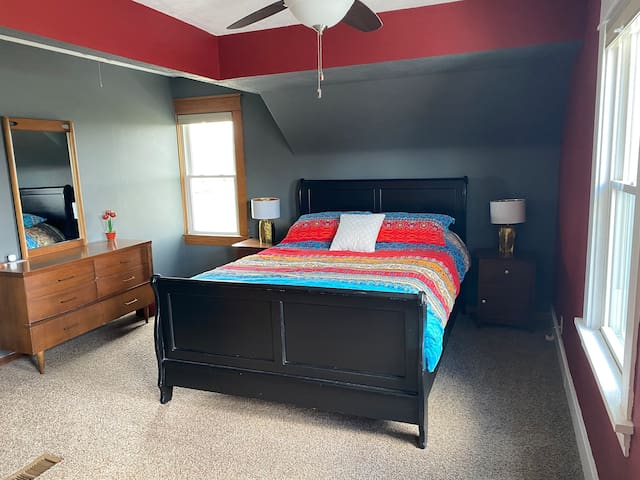 This bedroom includes a walk in closet, dresser and a comfy bed