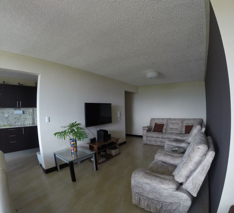 Sala con TV pantalla plana y teatro en casa.
