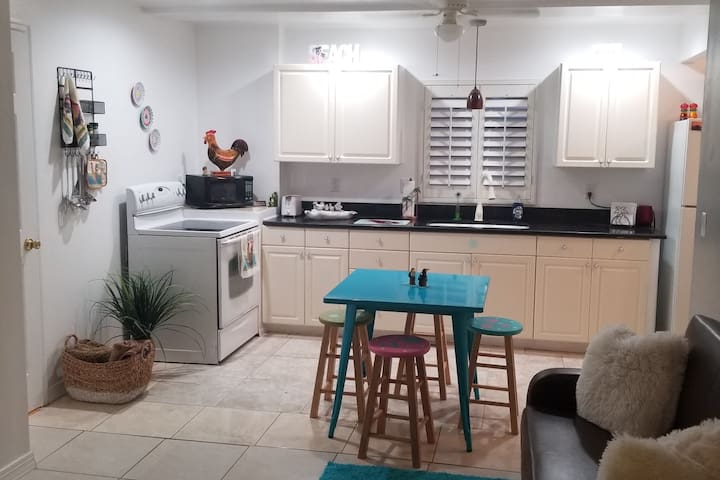 Our cozy kitchen is complete with flat top stove and full size refrigerator. A Key West style table and barstools adds to the fun atmosphere of Florida. Bright colors, clean atmosphere, outside seating and safe nieghbood surround  you.