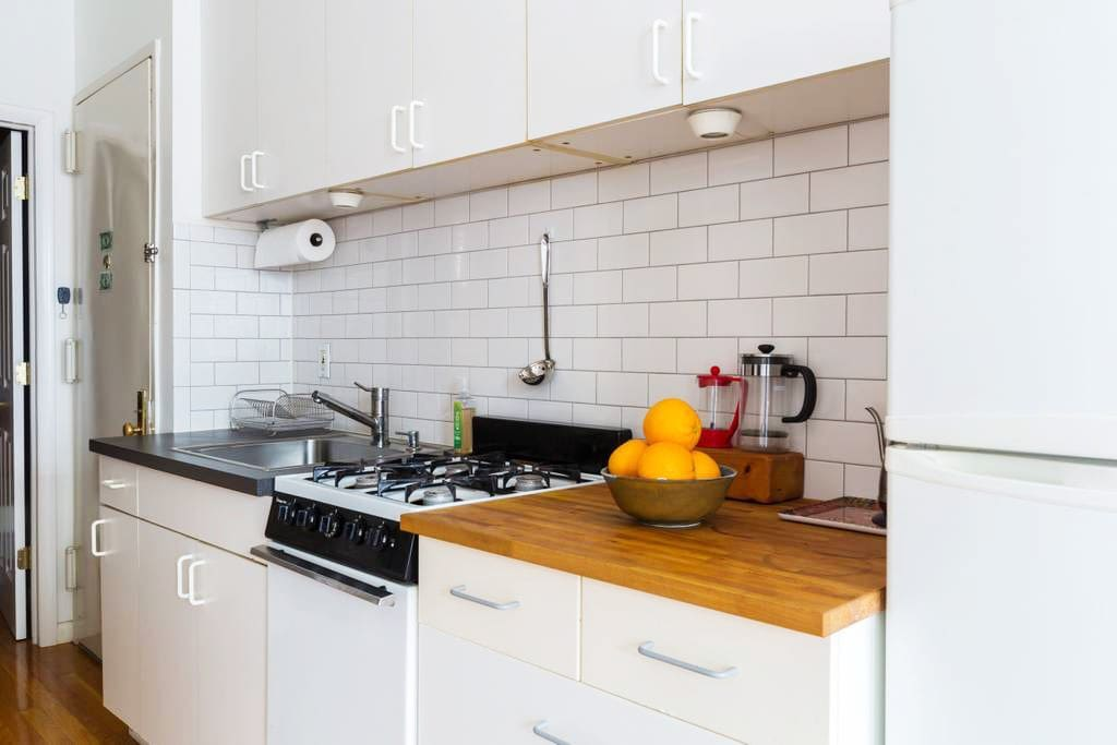 Gourmet Kitchen with oven, cooktop, pots & pans, full fridge, electric tea kettle and more