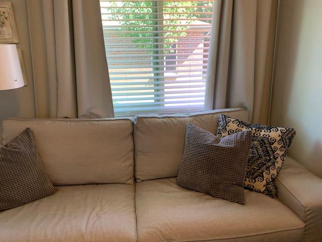 Full sofa with east facing window overlooking the backyard.