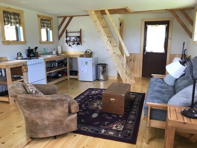 Main room with view of kitchen, stairs to loft and comfy futon and bucket chair. Futon unfolds to full size bed.