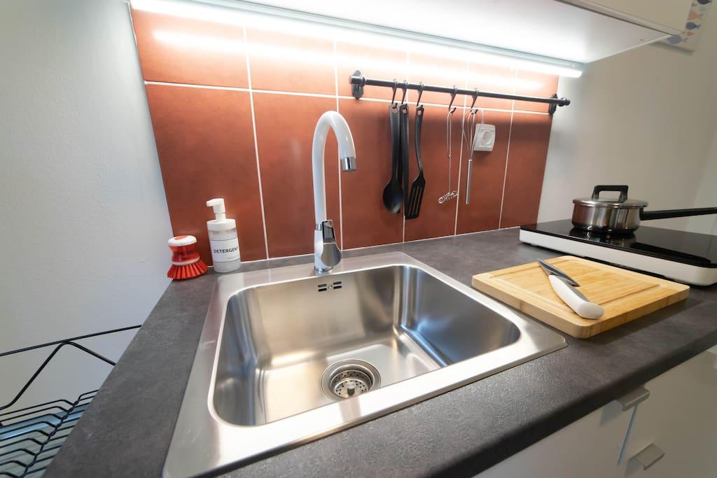 Crockery. Sink. Kitchen. Chopping Board. Knife. Cooking Utensils. Detergent. Hot Plate
