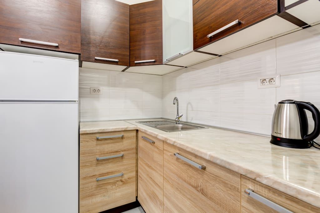 The kitchen is modernly equipped and includes a cooker, a cooker hood, a large fridge with a freezer.
