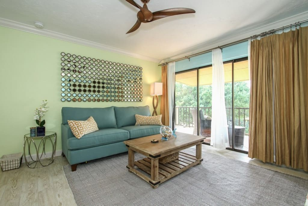 Beautifully decorated living space with queen sleeper sofa & ceiling fan.