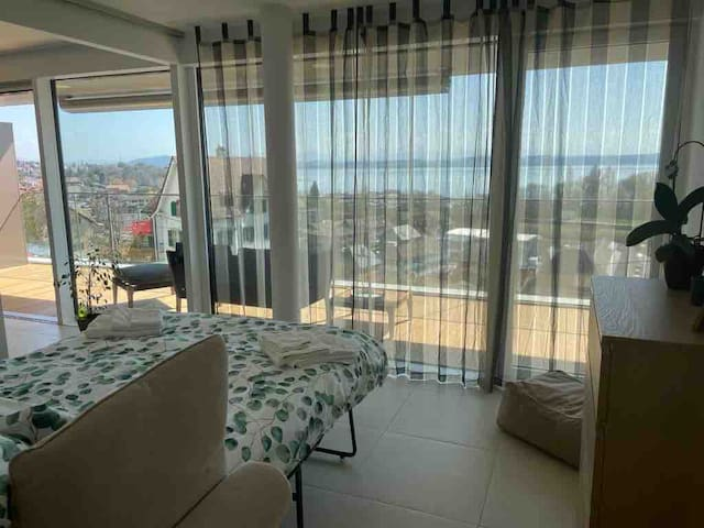 Small bedroom (12 m2) with sliding door to the living room and couch prepared as bed (140 cm) with balcony view