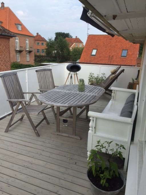 Roof top terrace with BBQ, recliners and bench.