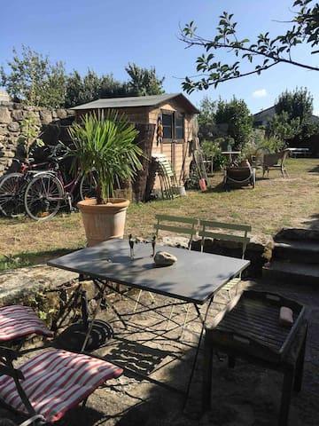 Maison côté jardin avec sa terrasse en pierre et cabane de jardin