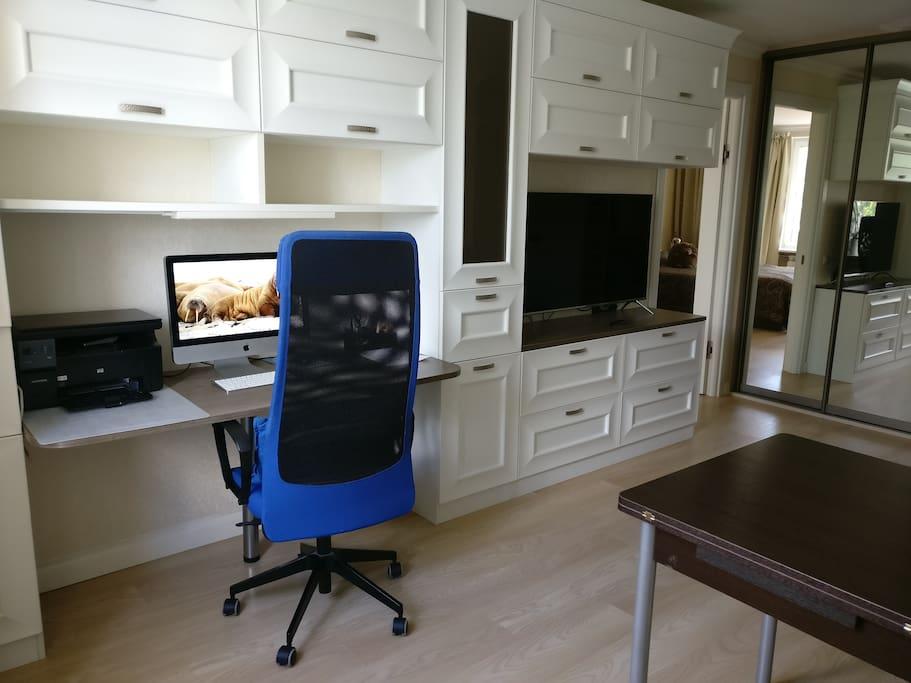 Гостиная комната. В комнате большой раскладной диван (160*200), телевизор со Smart TV, рабочее место с маленьким ноутбуком (компьютера на фото нет), обеденный стол (тоже раскладывается)