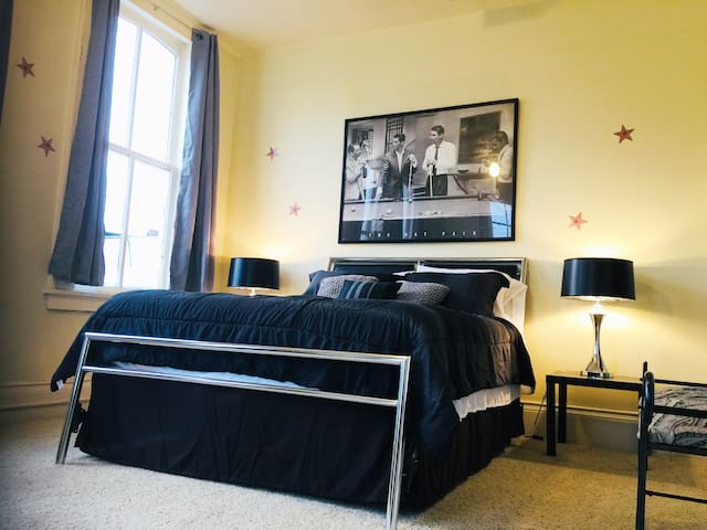 """Large bedroom with queen bed and lots of windows.  Enjoy the soothing sound machine on the nightstand if the """"downtown city life"""" gets too lively at night."""