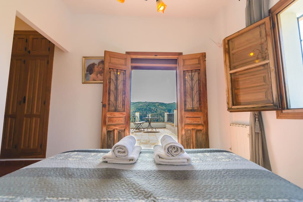 One of the bedrooms with doors to upper terrace and amazing views!