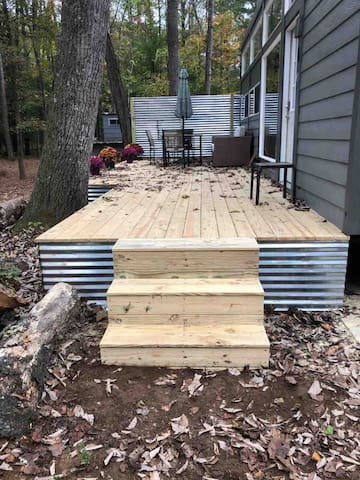 the tiny house has a HUGE deck with outdoor table and couch to enjoy the outside beauty.