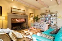 Sitting area in main house, cozy blankets and pillows, massive fireplace, books to read