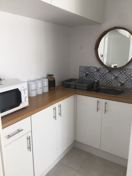 Kitchenette with microwave, a hotplate, mini fridge, coffee & tea and a small sink to wash dishes.