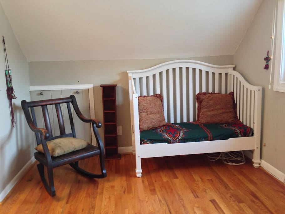 There's also a chair and a baby's bed that could be another sitting area.
