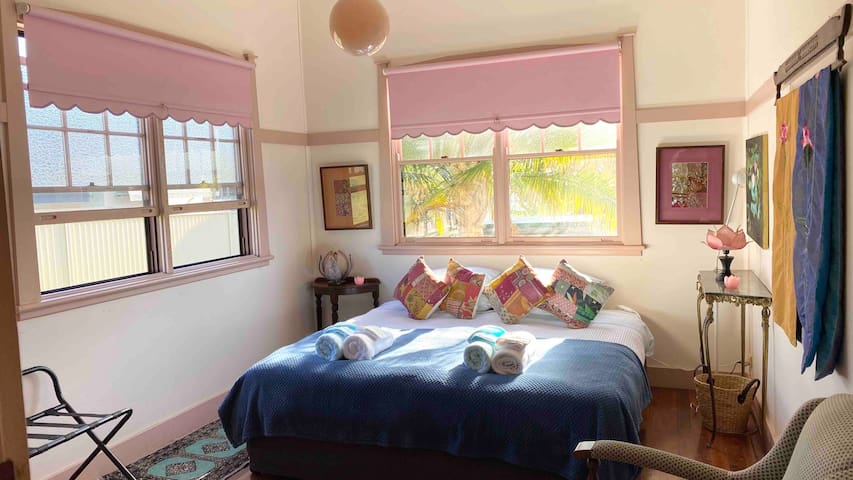 Large high ceiling bedroom with slash windows. King bed with quality sheets, bed covers and towels.