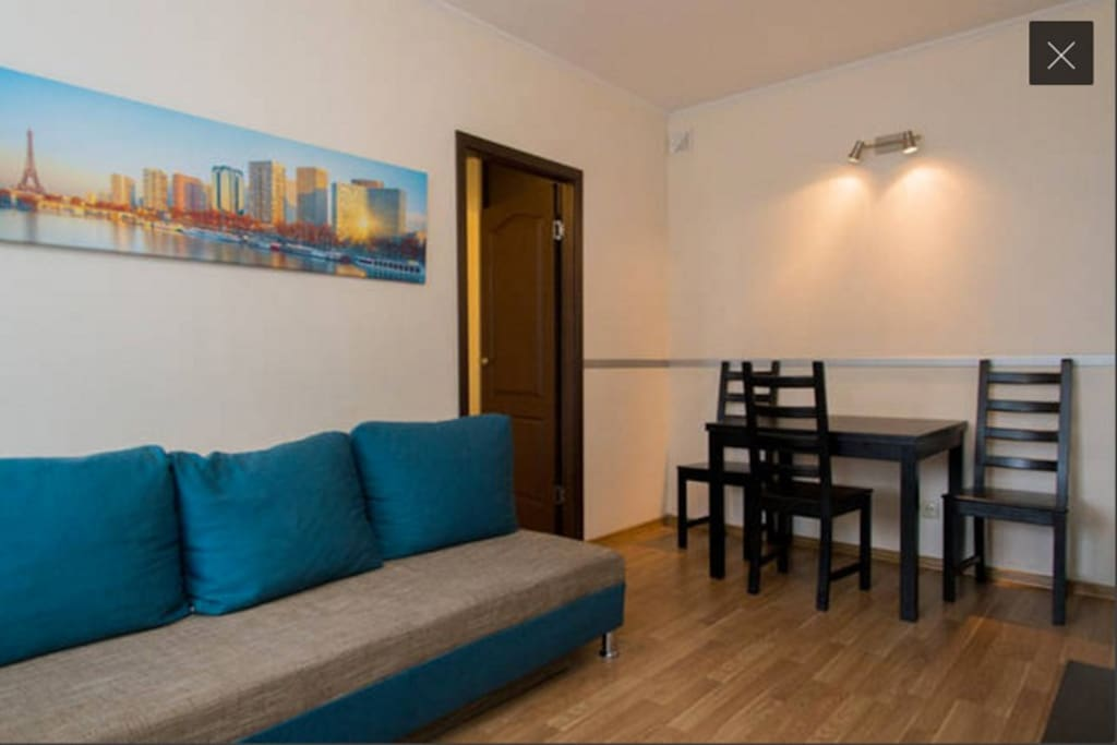 Living room with flat screen TV and comfortable sofa. Every apartment has free Wi-Fi