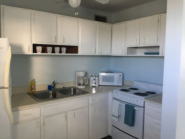 Equipped kitchen with cookware, dishware, microwave and refrigerator.