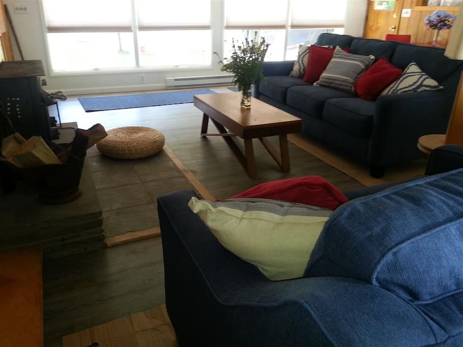 Family room with sofas, fireplace, and a vintage table for morning coffee as you watch eagles soar above the river