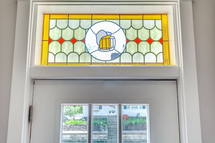 Custom stained glass featuring a beer mug sits above the front door.