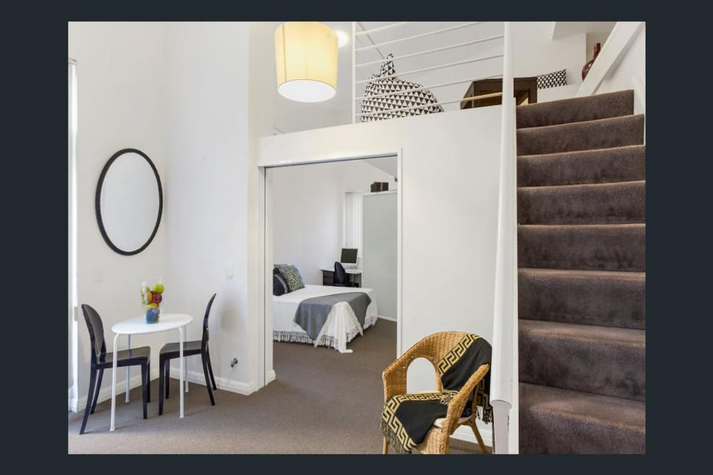 The sitting area of the apartment next to the kitchen, through to the bedroom. Note the loft upstairs, where I have a TV and couch that converts to a double bed. (I currently have a couch and a wall unit downstairs.)