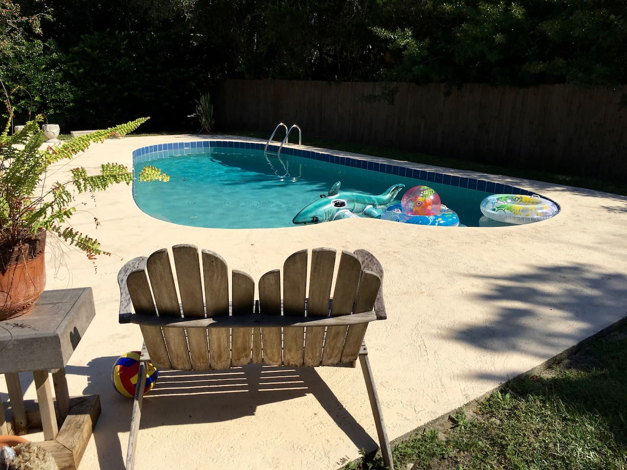 Backyard pool surrounded by privacy fence.