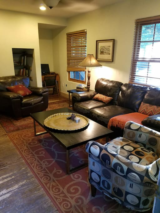 The living area has plenty of seating and features a desk and book/game nook.