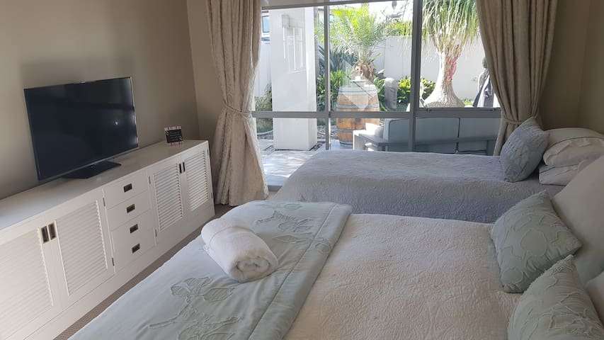 Second bedroom with double and single bed leading out to a  private secluded courtyard