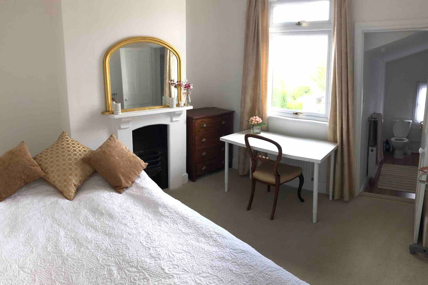 Double bedroom with work desk and view through to the en suite with Bath and shower, sink and WC