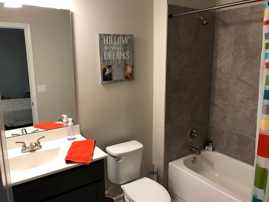 Private full bathroom with tile floors and shower.